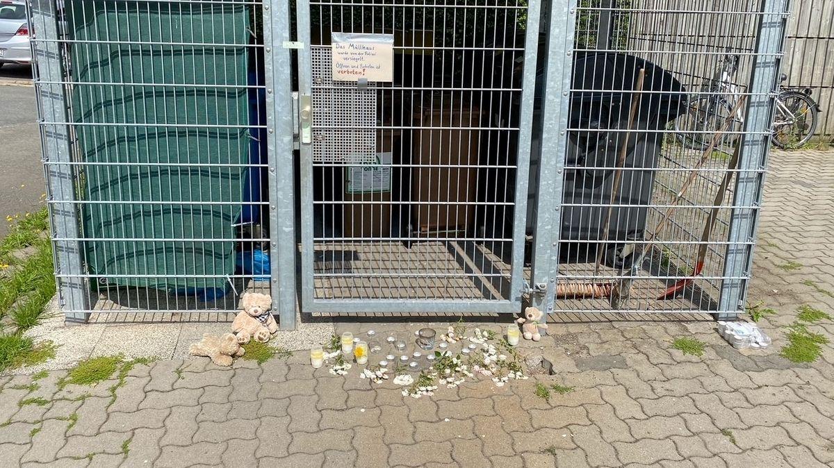"""Kerzen und Teddybären liegen vor dem Fundort, an dem das tote Baby entdeckt wurde. An der Gittertür steht auf einem Schild """"Zutritt verboten""""."""