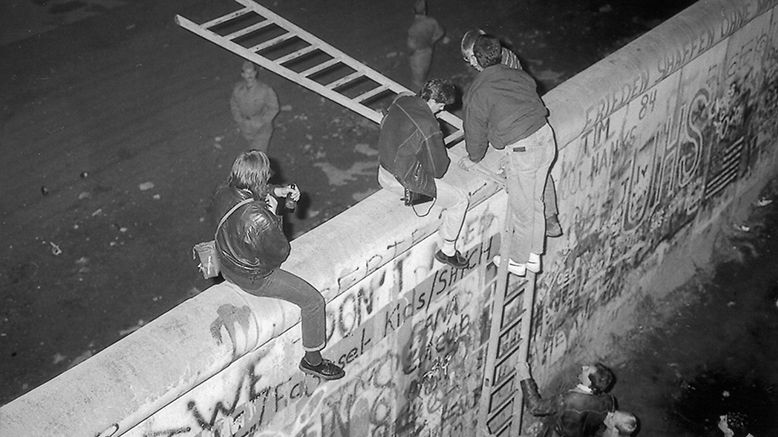 Menschen klettern mit zwei Leitern über die Mauer