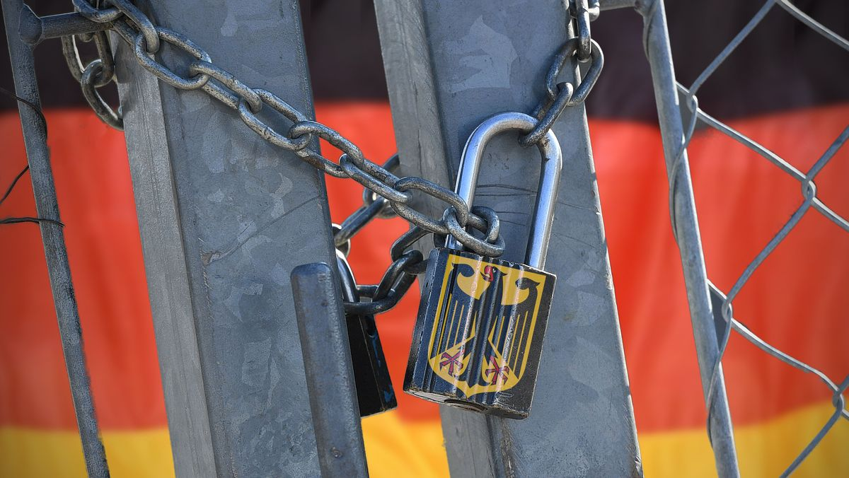 Vorhängeschloss mit Bundesadler um ein Tor, hinter dem die deutsche Flagge zu sehen ist (Symbolbild)