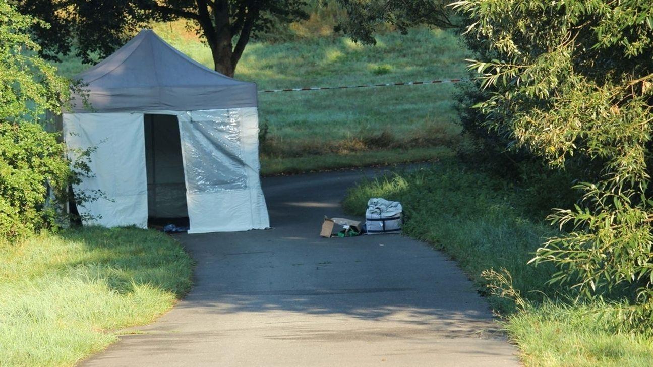 Neben einem Radweg ist ein weißes Zelt aufgestellt, dahinter ein weiß-rotes Absperrband