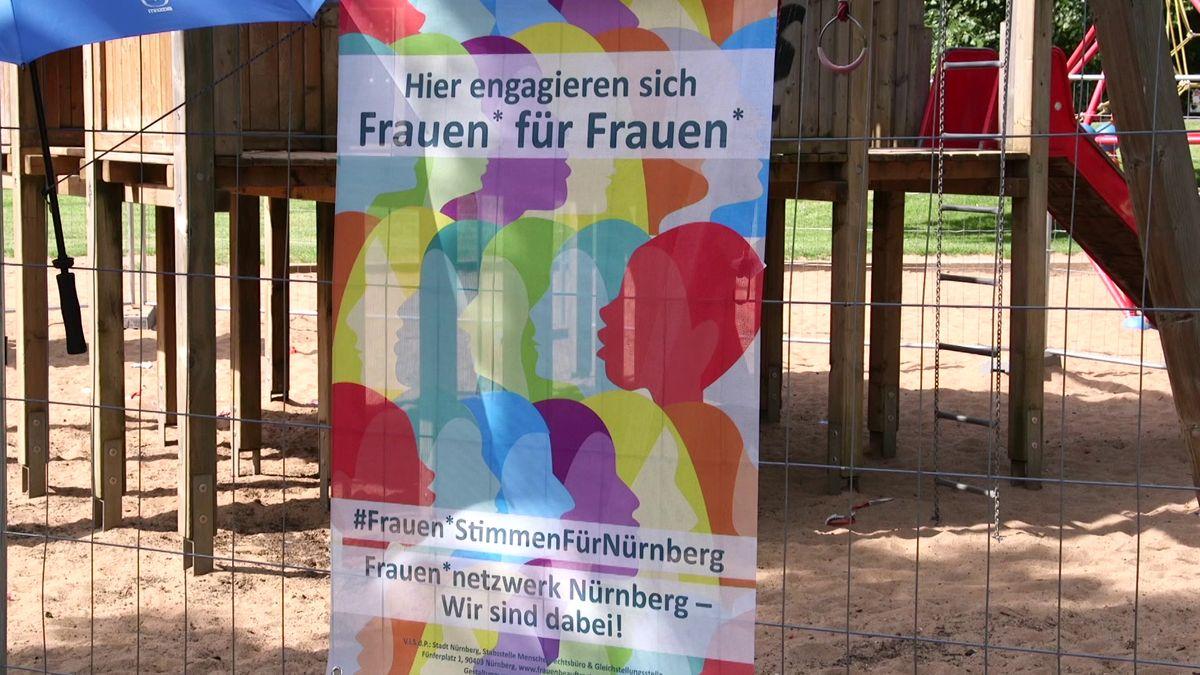 """Ein buntes Schild an einem Klettergerüst mit dem Text """"Hier engagieren sich Frauen für Frauen"""""""
