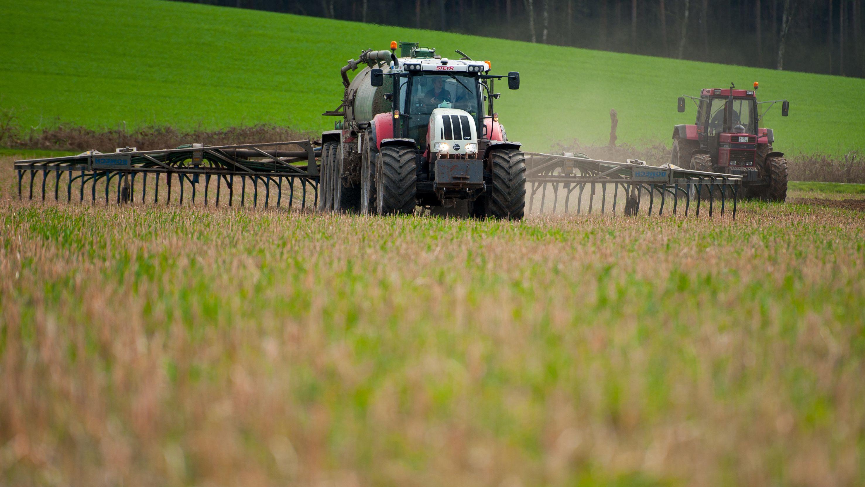 Landwirt bringt auf Wiese Gülle aus