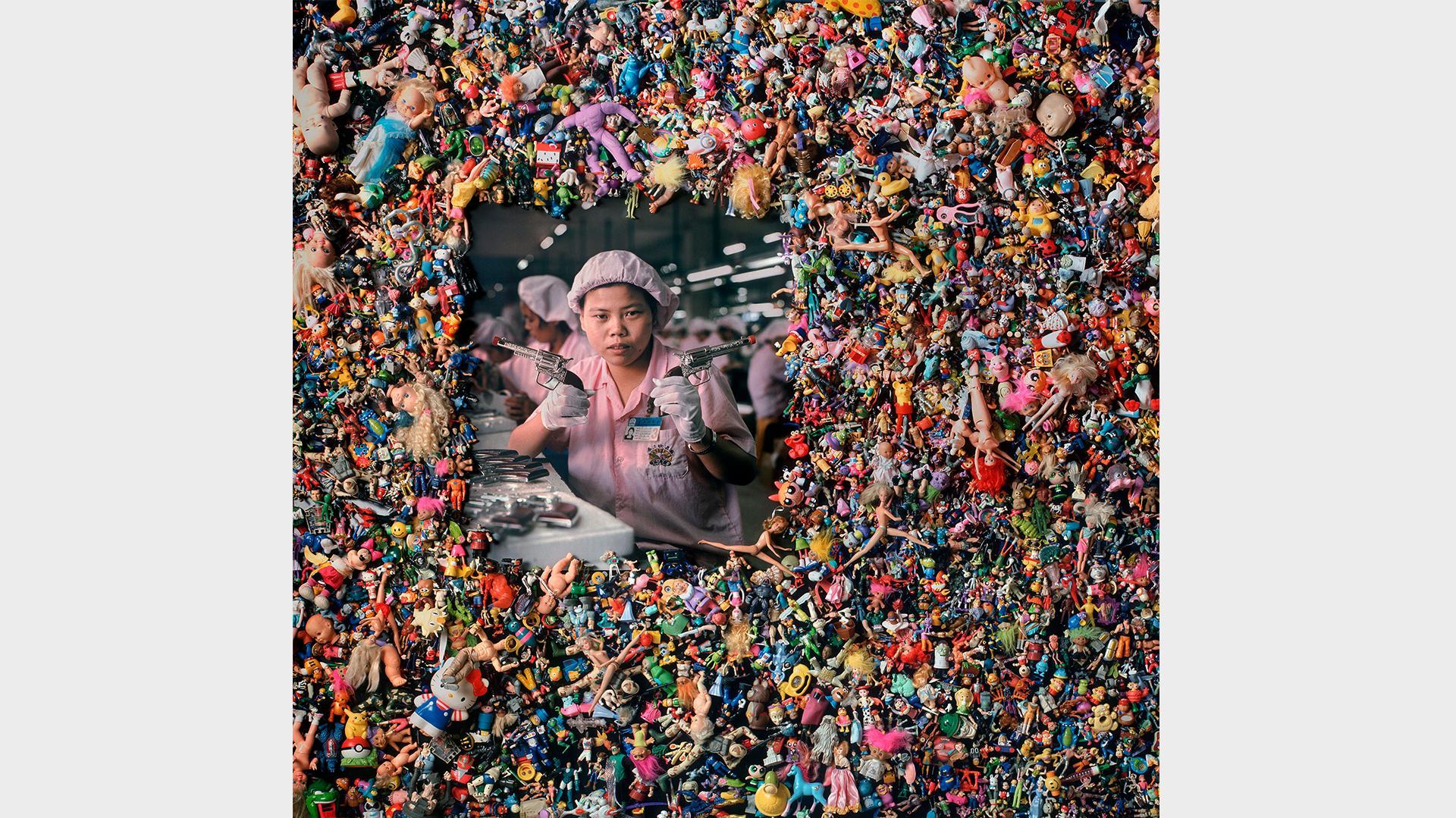 Ein Foto einer chinesischen Spielzeug-Fabrik-Arbeiterin umgeben von Unmengen an Plastik-Spielzeug