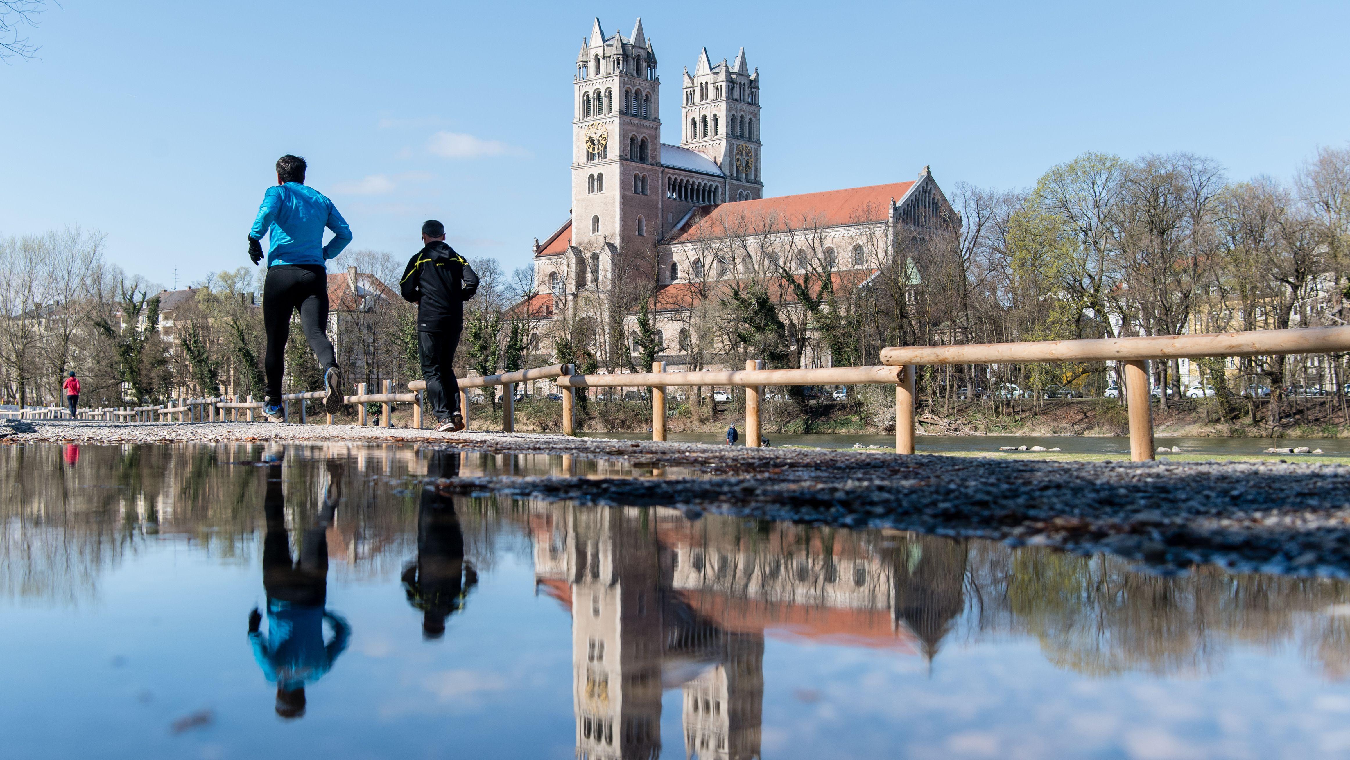 Zwei Jogger laufen während der Corona-Krise an der Münchner Kirche St. Maximilian vorüber.