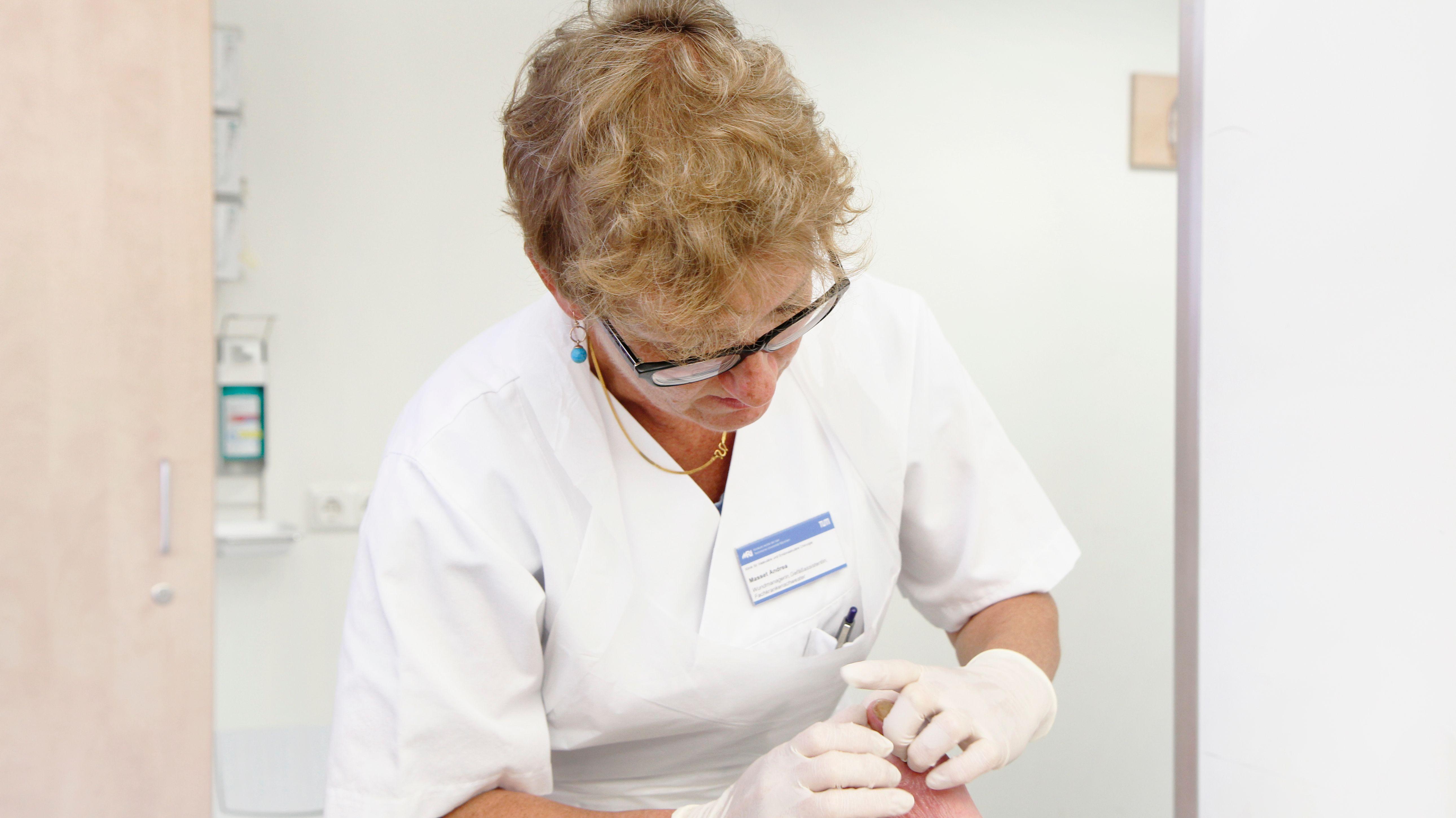 Eine Krankenschwester bei der Wundversorgung eines Patienten.