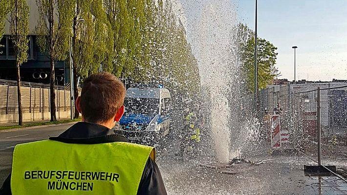 Feuerwehrmann betrachtet Fontäne auf Straße in Sendling