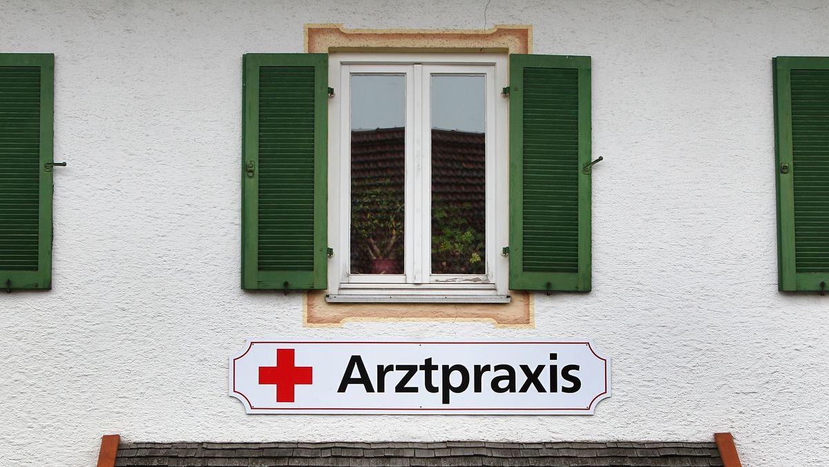 Ein Schild an einem älteren Haus auf dem Land weist auf eine Arztpraxis hin