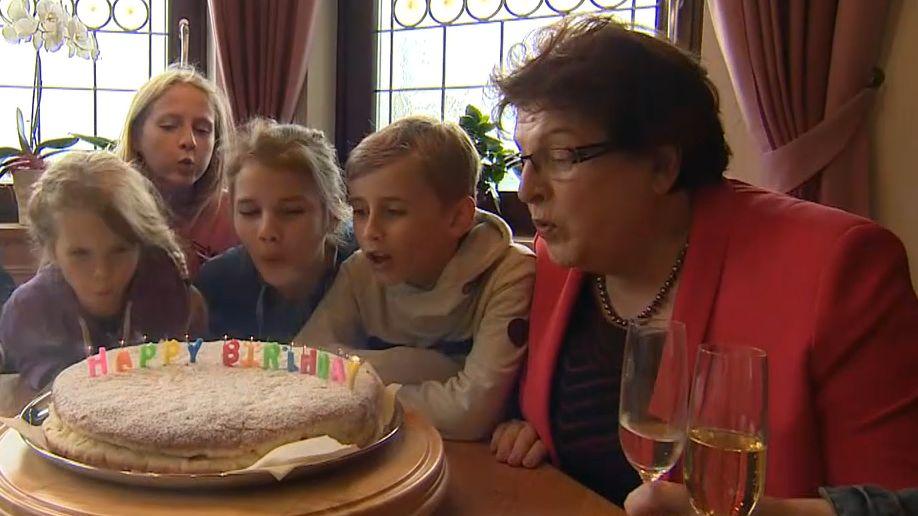 Barbara Stamm sitzt mit Kindern und einem Mann um einen Tisch herum und bläst Kerzen auf einem Kuchen aus.