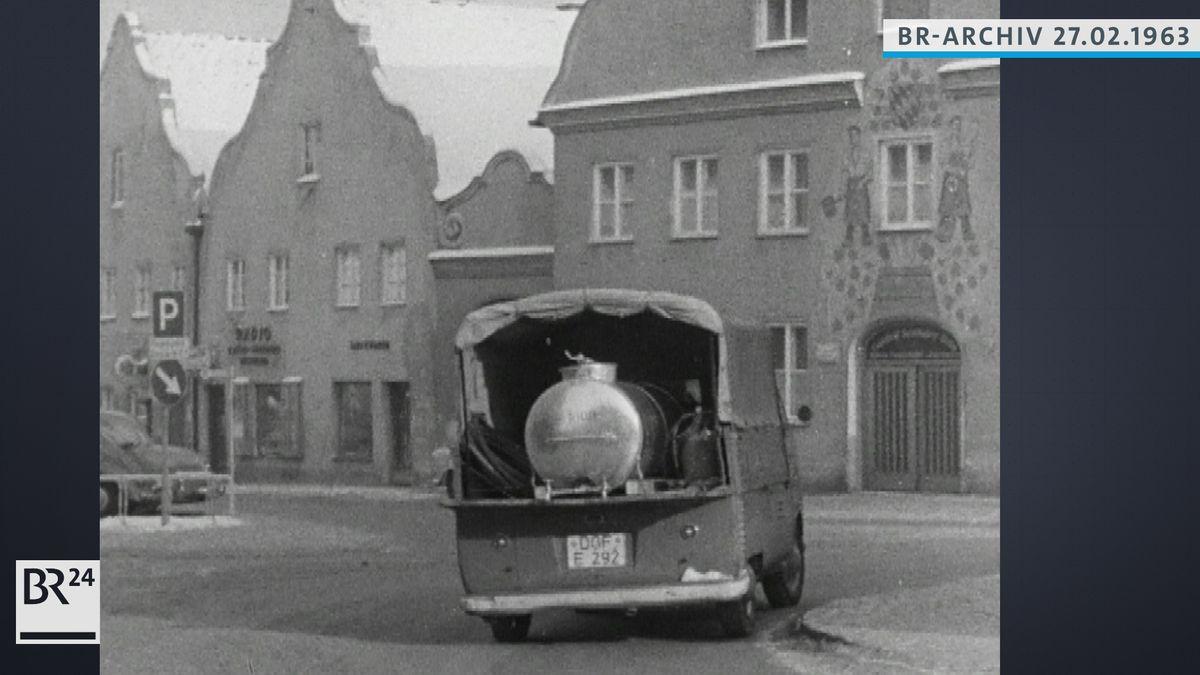 Ein VW-Transporter mit offener Ladefläche transportiert ein Fass mit Trinkwasser für die Wasserversorgung der Anwohner