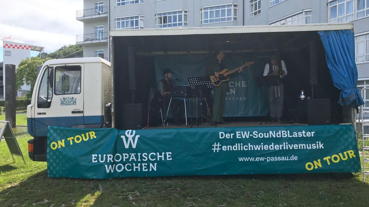 """""""Bitte mit Abstand geniessen"""", steht auf dem Schild der Europäischen Wochen. Im Hintergrund ist der Lkw mit der mobilen Bühne zu sehen."""