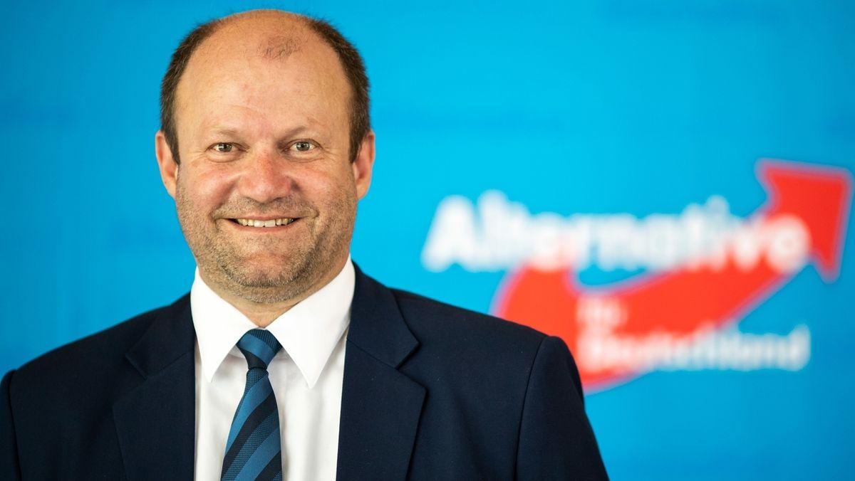 Markus Bayerbach steht vor einer Wand mit AfD-Logo