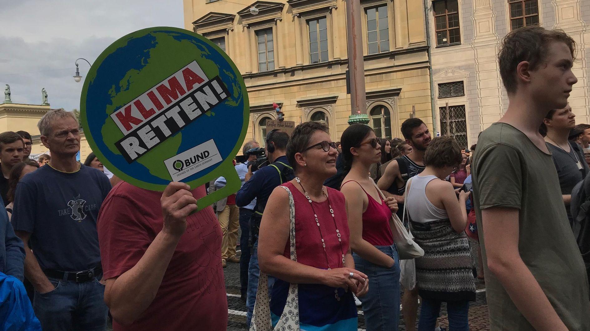 """Demonstranten von """"Munich for Future"""" unter wolkemverhangenen Himmel auf dem Münchner Odeonsplatz. Ein Demonstant hält eine Schdeibe hoch mit der Aufschrift """"Klima Retten!"""" BUND"""