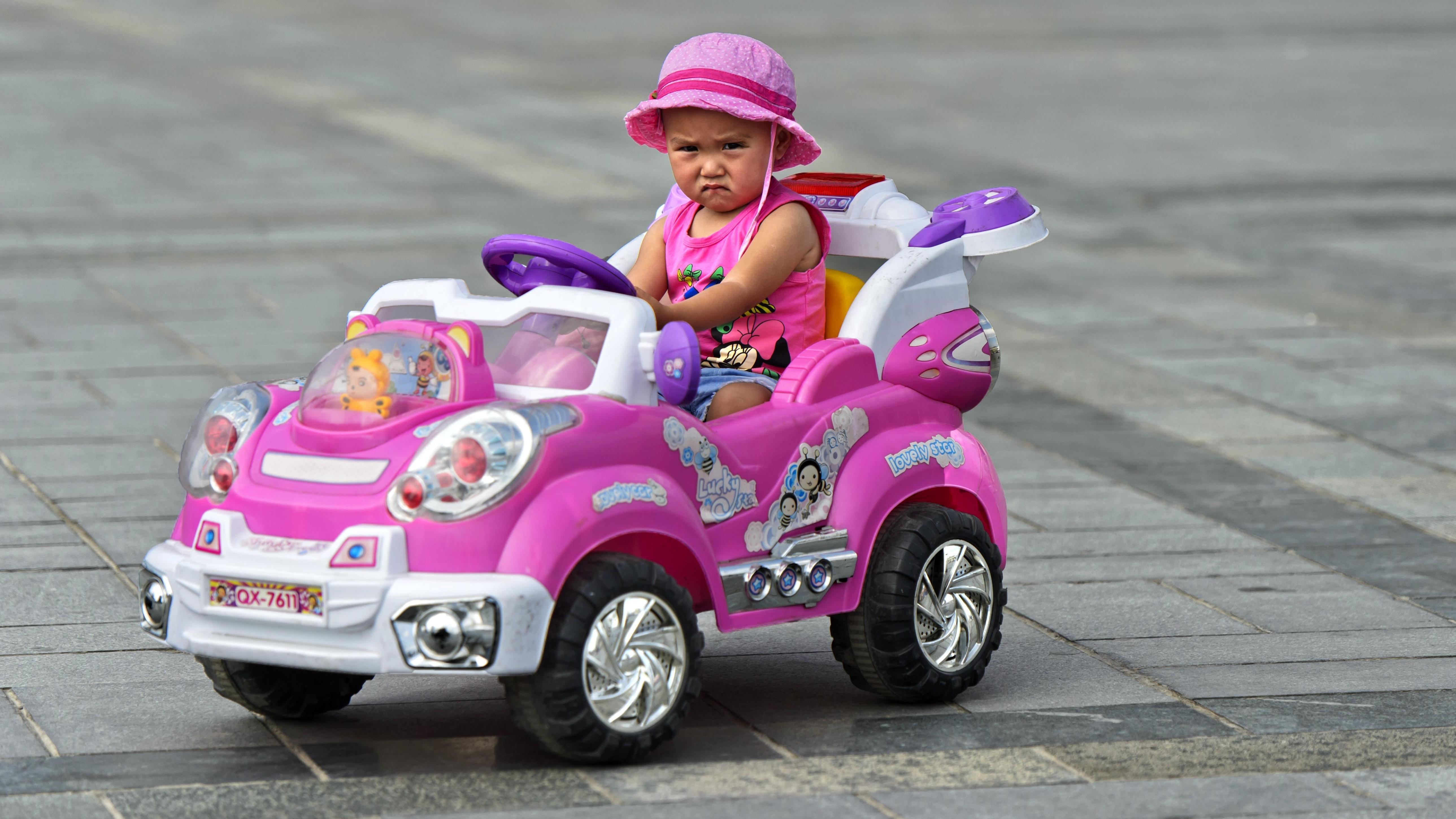Mädchen in einem pinken Auto mit pinken Klamotten.