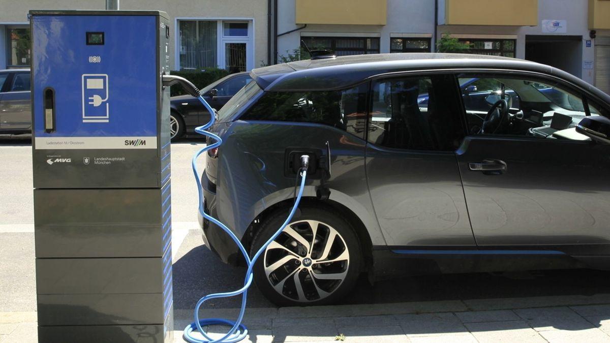 Ein blaues Ladekabel zieht sich von der Ladesäule zum Auto.