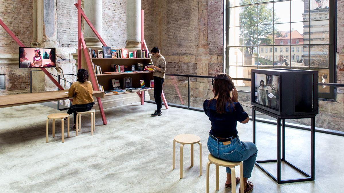 Blick in einen Raum mit Monitoren und Buchregal