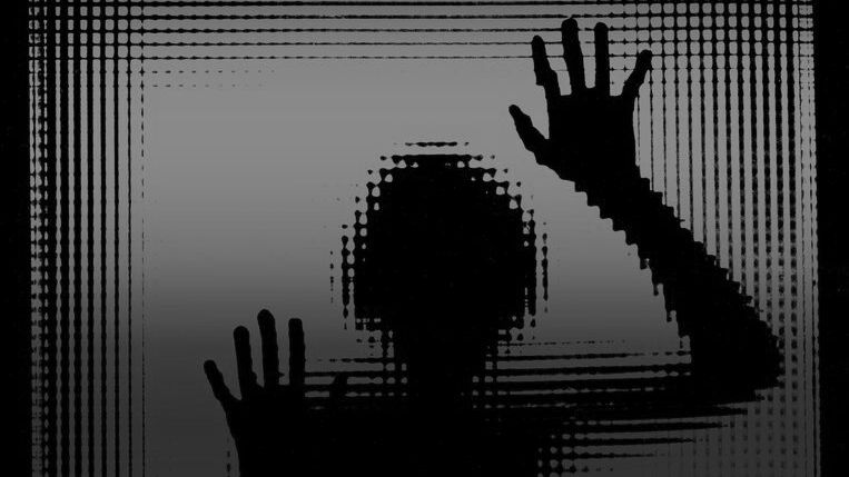 Der Umriss eines Kindes hinter einer Glastür. Foto in schwarz-weiß.