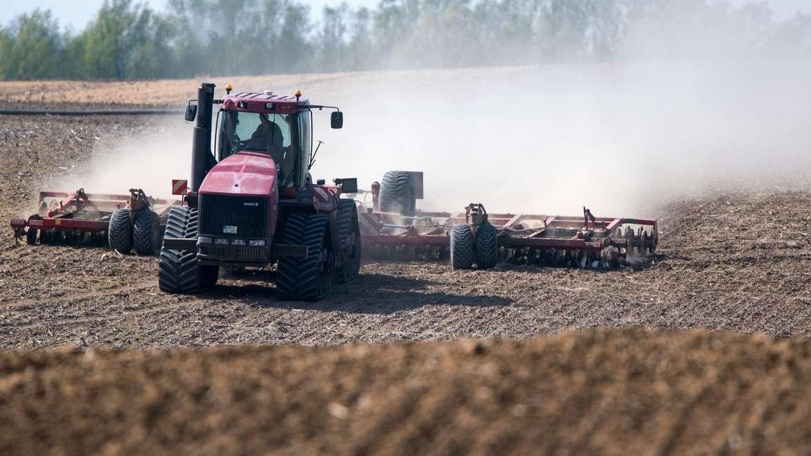 Ein Bauer pflügt sein Feld und zieht dabei - weil der Boden sehr trocken ist - eine große Staubwolke hinter sich her