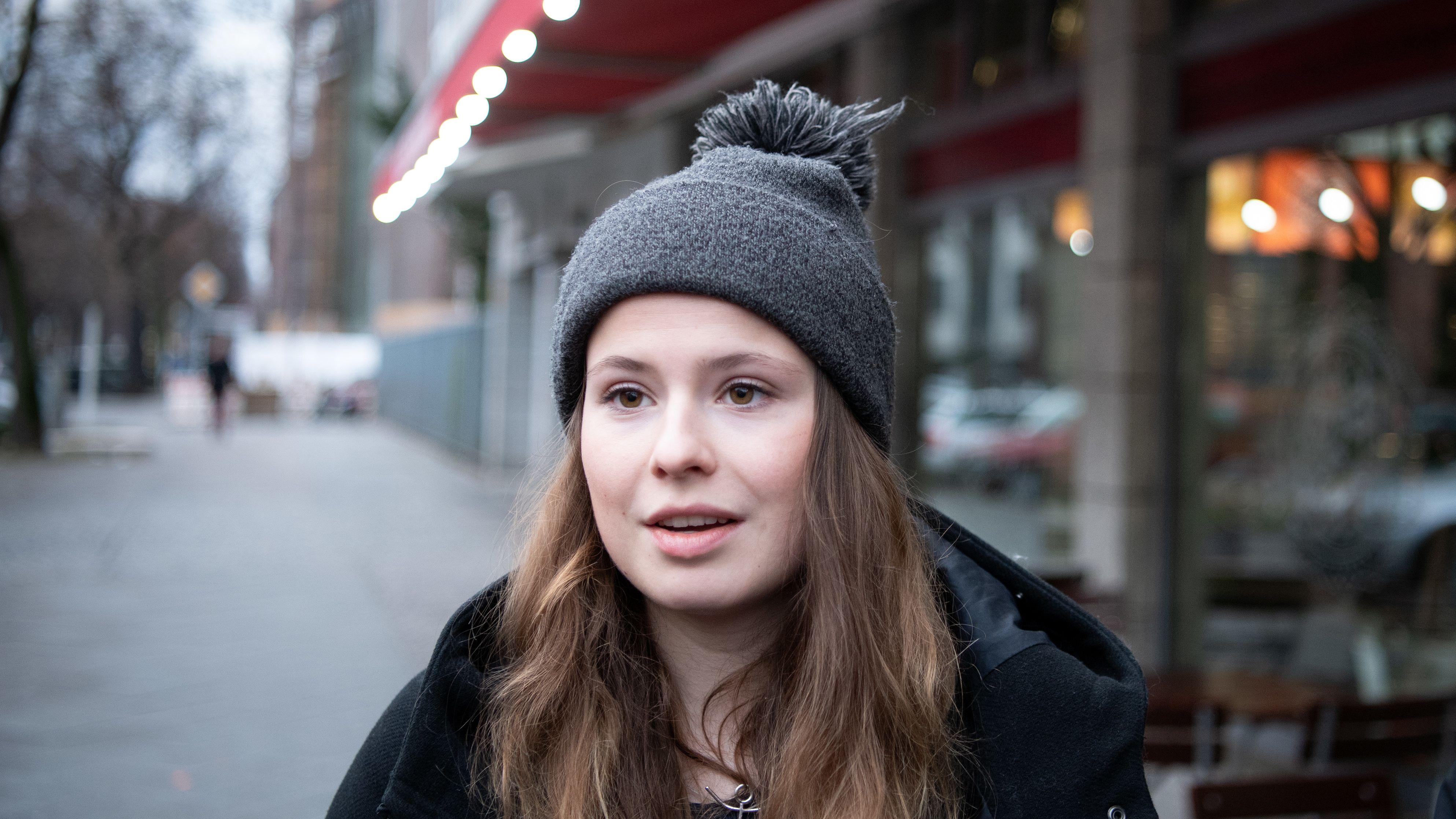 Luisa Neubauer, mit offenen braunen Haaren, darüber trägt sie eine graue Bommelmütze.