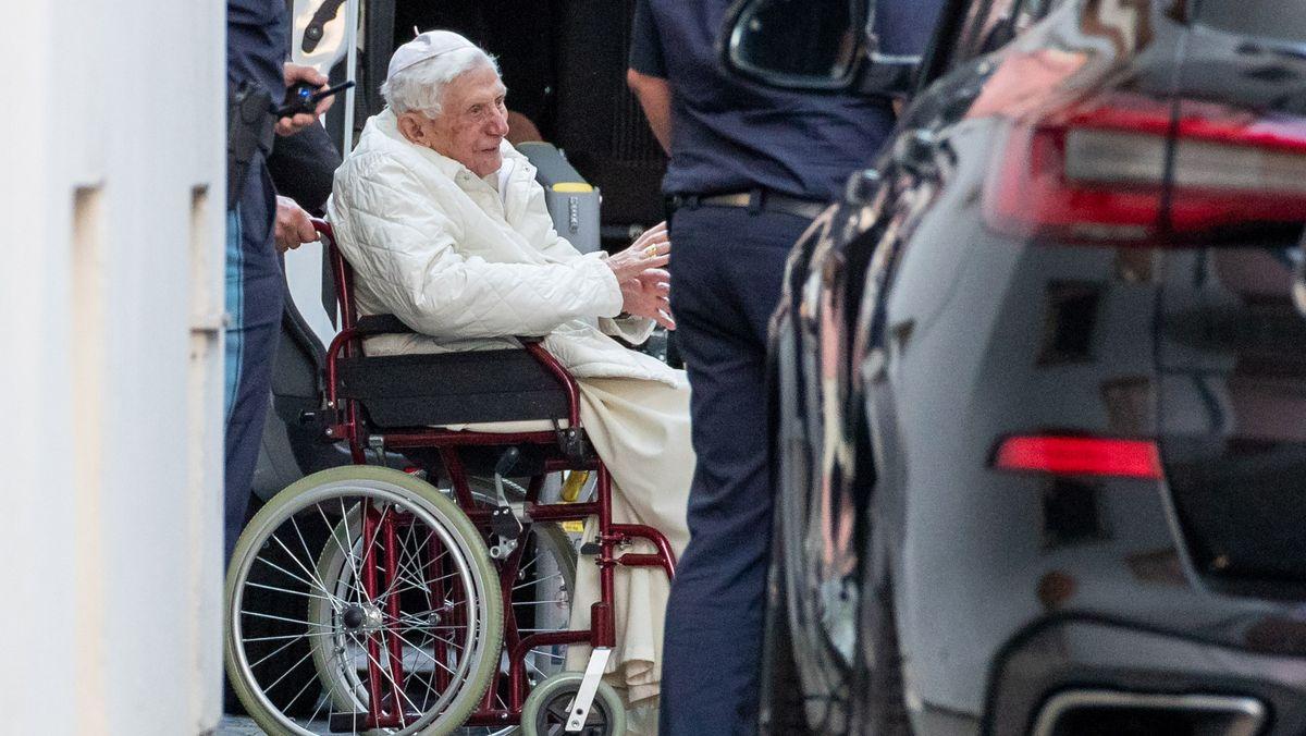 Zu Besuch beim kranken Bruder in Regensburg: Der emeritierte Papst Benedikt XVI wird mit einem Rollstuhl in einen Bus geschoben.