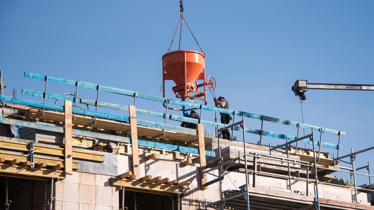Arbeiter leeren auf einer Baustelle an dem Neubau von einem Mehrfamilienhaus ein Behältnis für Beton.