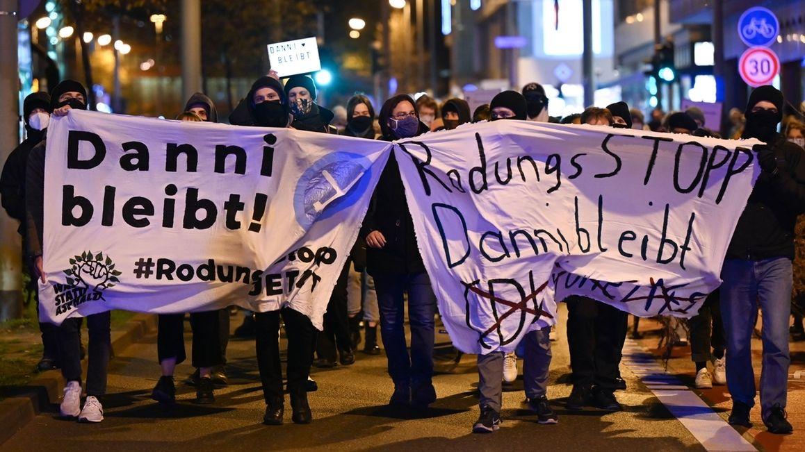 """Proteste gegen A49 - Frankfurt am Main Teilnehmer einer Demonstration gegen den Ausbau der A49 halten in der Frankfurter Innenstadt während eines Demonstrationszuges Plakate mit der Aufschrift """"Dani bleibt"""" und """"Rodungsstopp Danni bleibt"""". Die Demonstration richtet sich gegen die Rodung des Dannenröder Forsts. Das alles trägt die Fraktion der Grünen mit, da sie in Hessen regiert."""