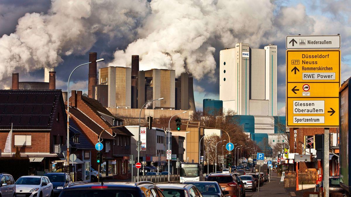 Eine Straße in Niederaussem mit Braunkohlekraftwerk im Hintergrund.