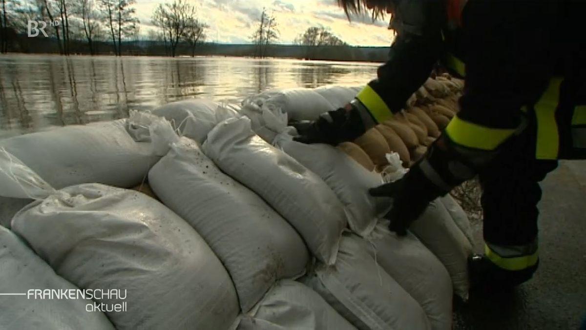 Ein Feuerwehrmann schichtet Sandsäcke an einem Flussufer auf.