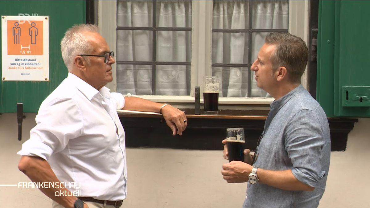 Zwei Männer trinken miteinander ein Bier.