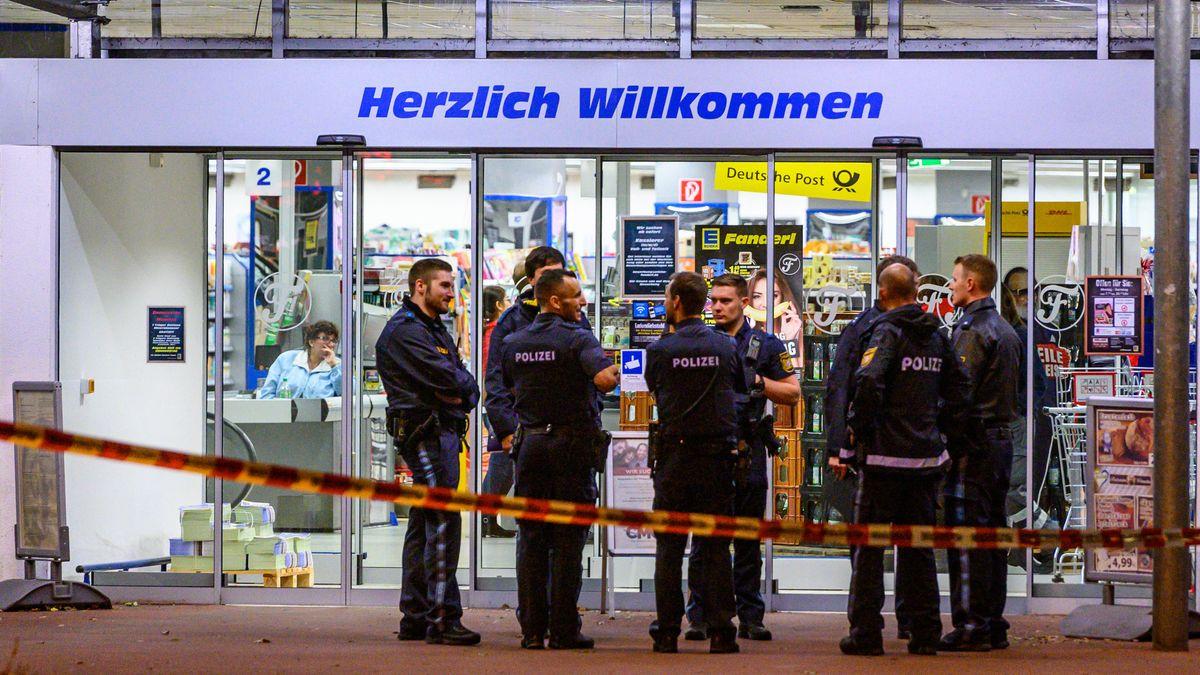 Polizisten stehen am Abend der Tat vor dem Supermarkt