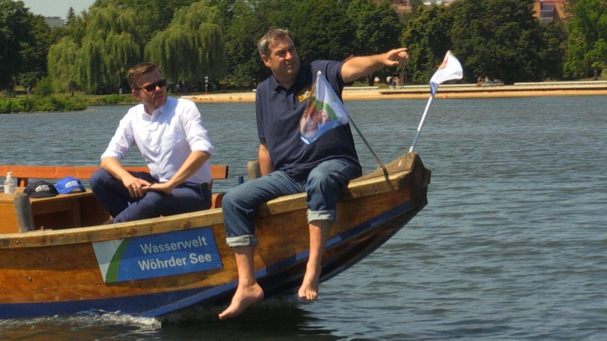 Markus König und Markus Söder sitzen auf dem Bug eines Bootes und fahren über den Wöhrder See.