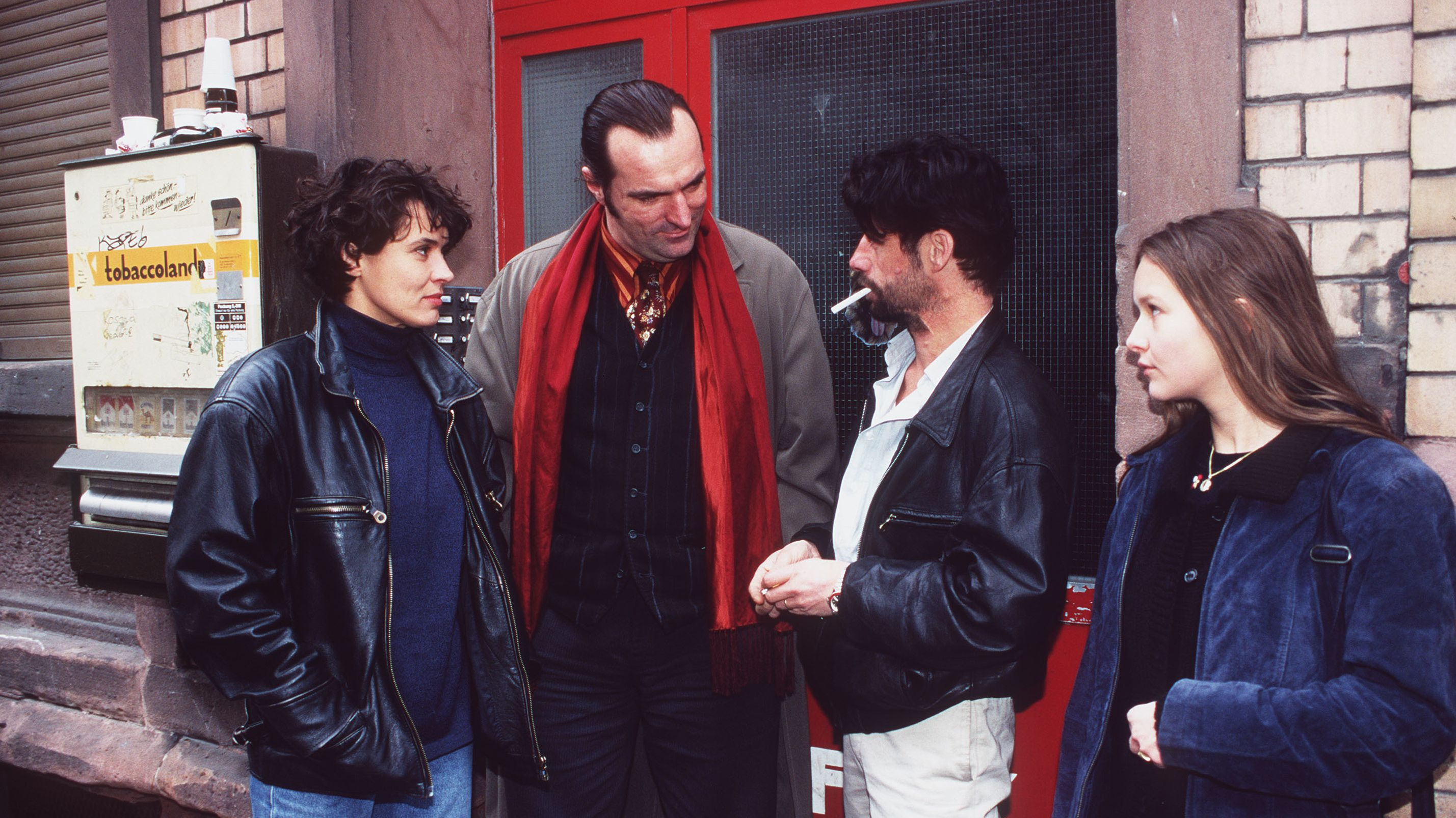"""Zwei Frauen und zwei Männer stehen in einem Hauseingang vor einer Roten Tür. Szene aus dem Tatort """"Engelchen flieg"""""""
