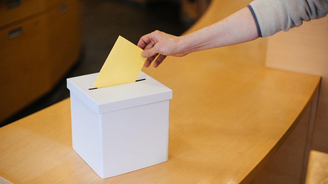 Jemand wirft einen Wahlschein in eine Wahlurne. (Symbolbild)