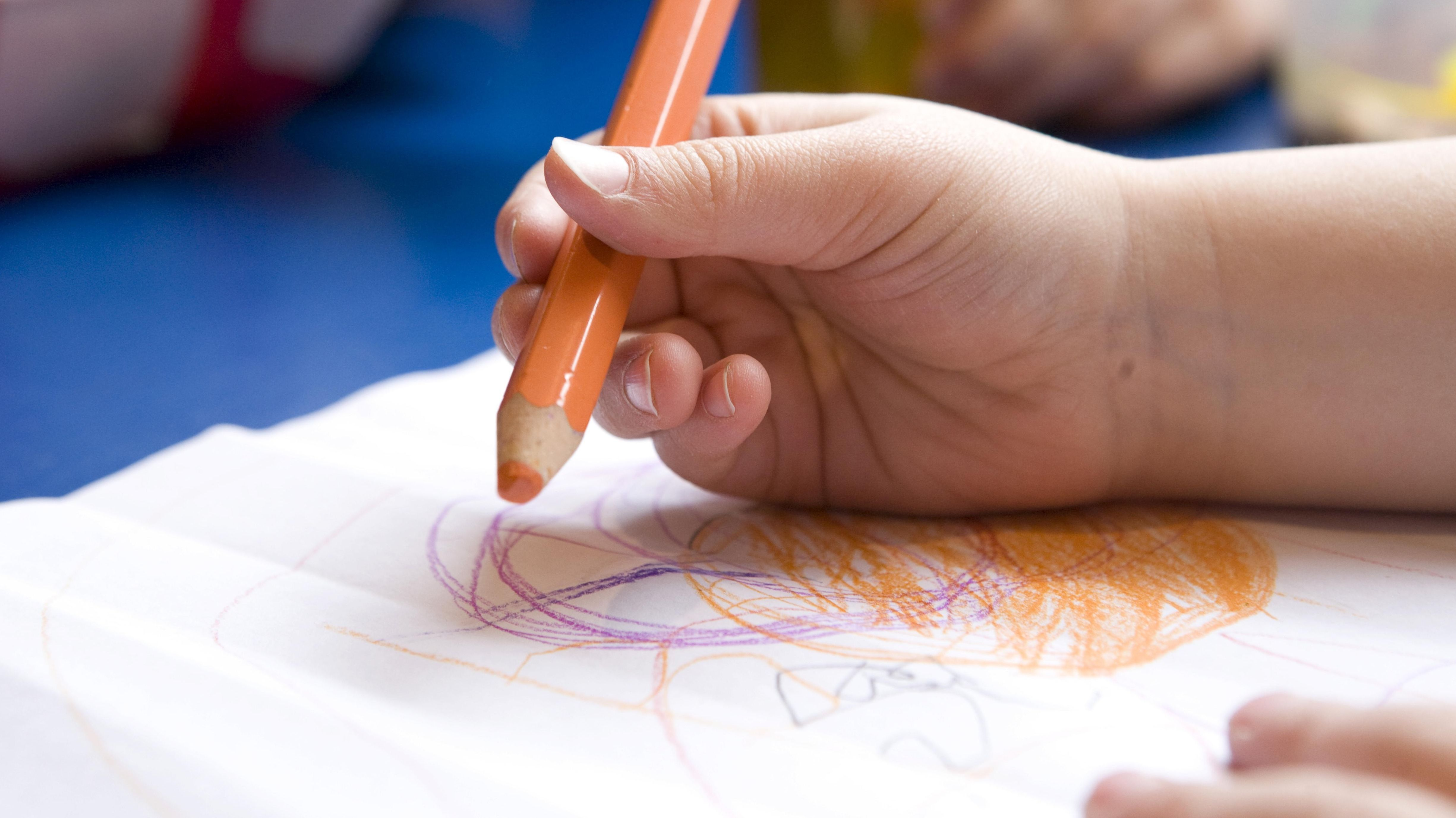Ein Kind malt mit einem Buntstift.