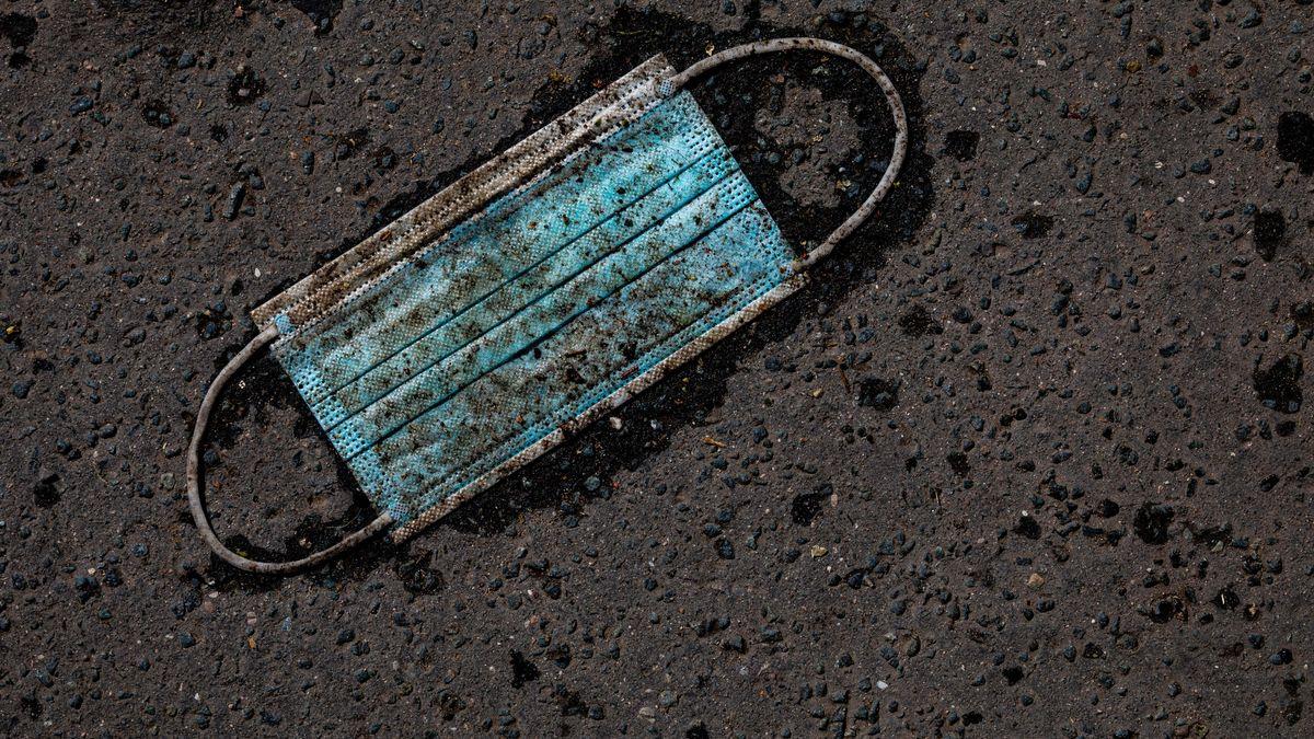 Symbolfoto Maskenaffäre: Eine stark verschmutzte Maske liegt auf dem Asphalt.