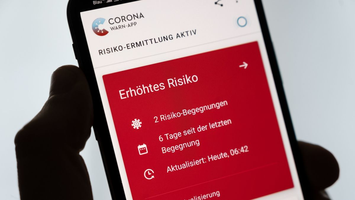 Ein Mann hält ein Smartphone in der Hand, auf dem die Corona-Warn-App ein erhöhtes Risiko anzeigt