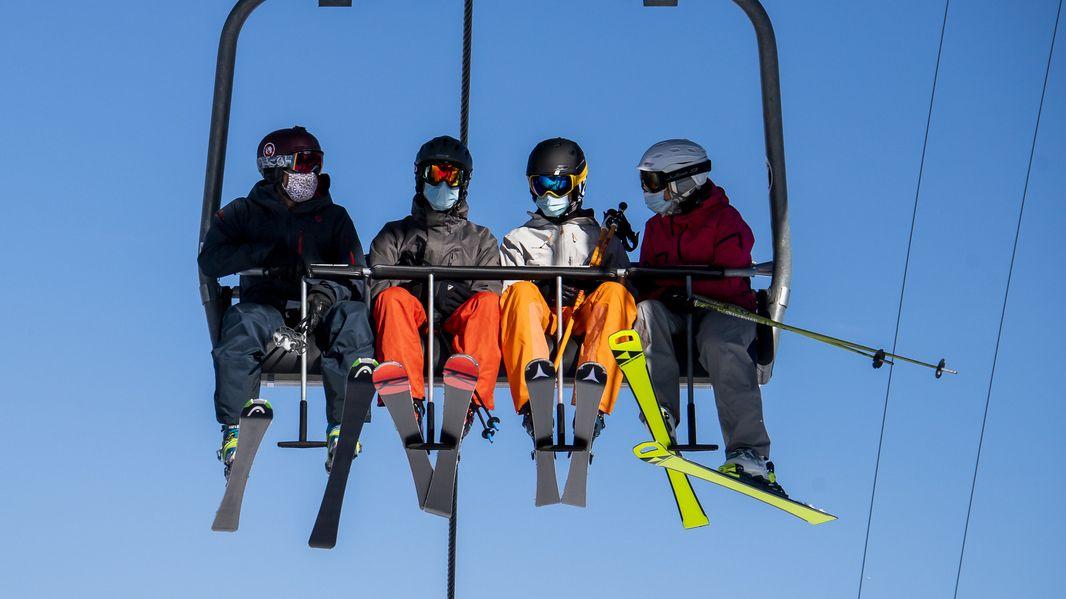 Skifahrer mit Masken in einem Sessellift in der Schweiz.