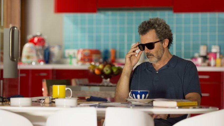 Hauptdarsteller Antonio Banderas sitzt mit Sonnenbrille an einem Küchentisch