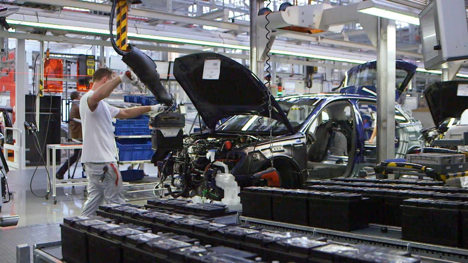 In einer Montagehalle baut eine Fachkraft PKW-Teile zusammen.