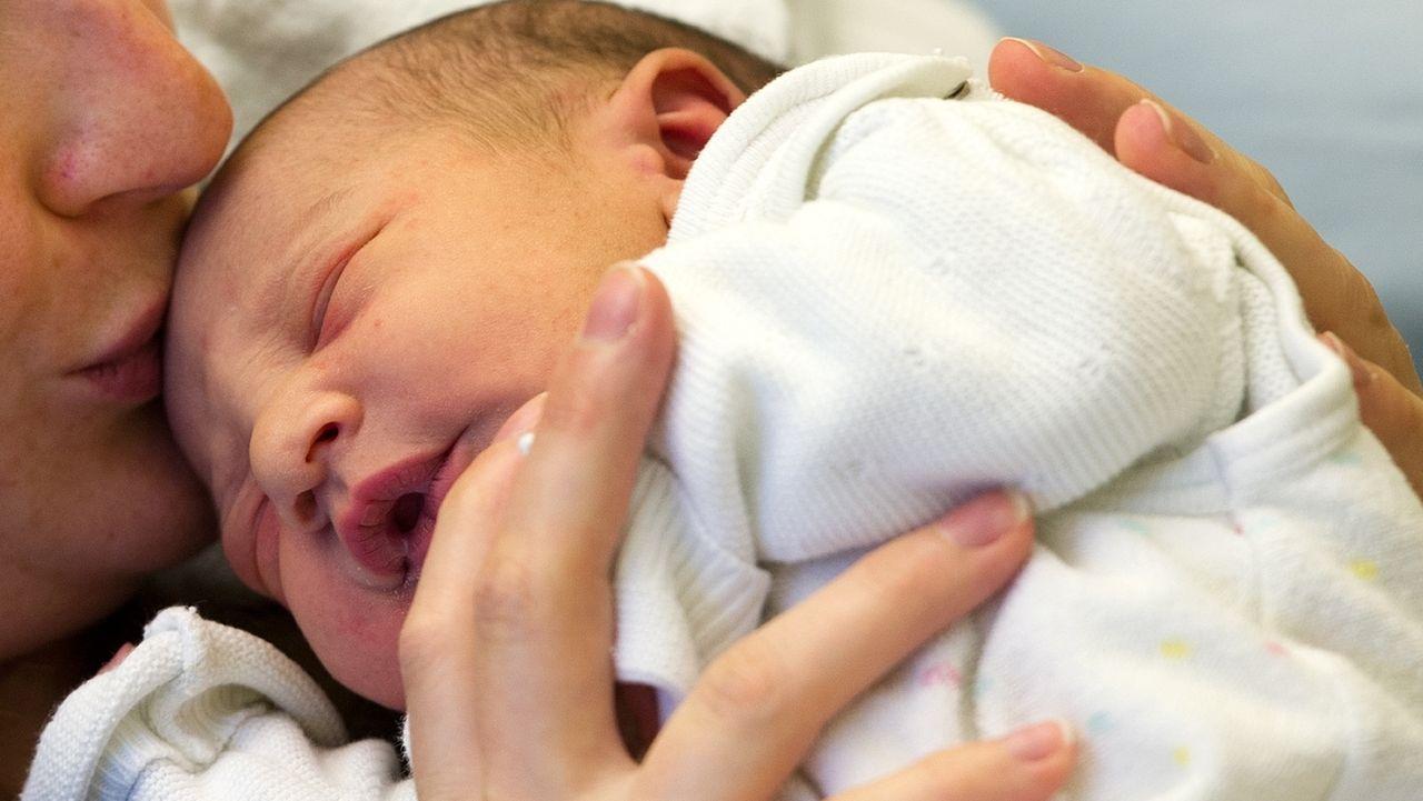 Neugeborenes im Arm der Mutter