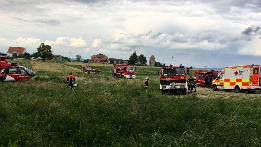 Mehrere Fahrzeuge von Einsatzkräften und ein Rettungshubschrauber stehen auf einer Wiese. In der Nähe ist ein junger Mann in einer Ruine abgestürzt.