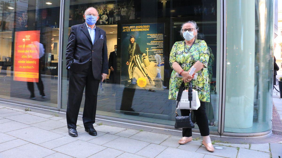 Opernfan Ellen Fleischmann steht vor dem Kartenverkauf, mit Mundschutz und männlicher Begleitung