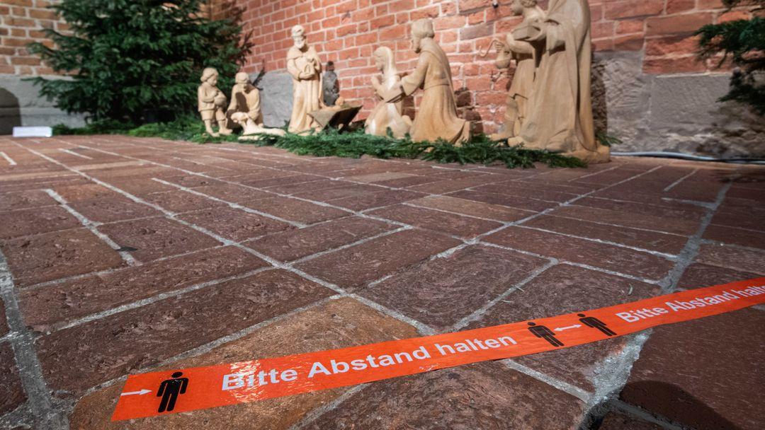 """Klebeband mit der Aufschrift """"Bitte Abstand halten"""" klebt vor einer Weihnachtskrippe in einer Kirche"""