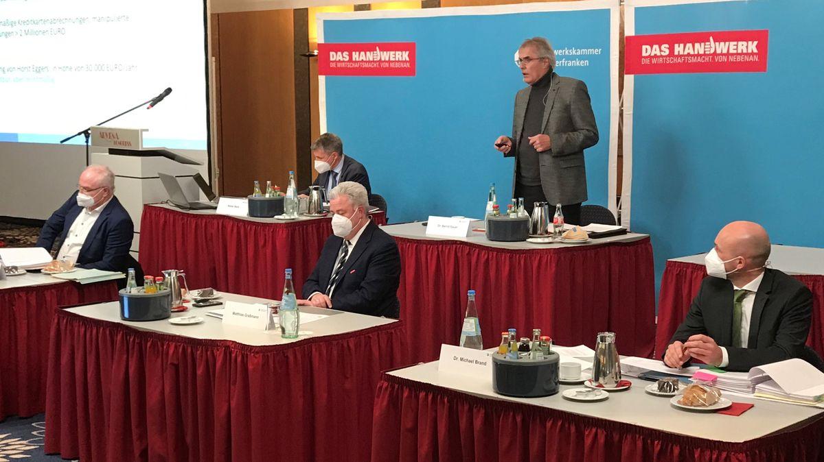Vier Männer mit Mundschutz sitzen an roten Tischen, dahinter steht ein Mann und spricht.