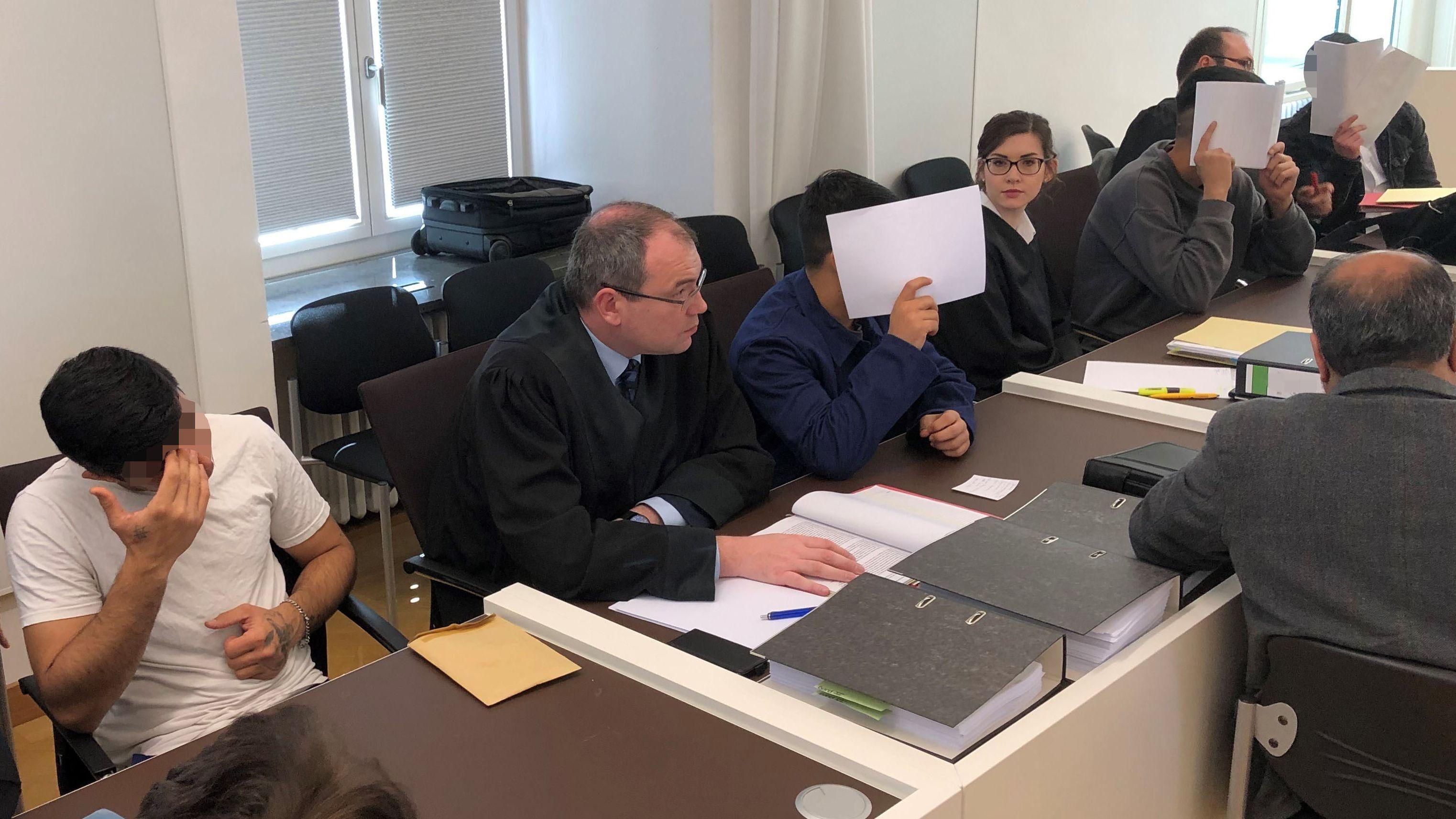 Die vier Angeklagten und ihre Verteidiger im Gerichtssaal