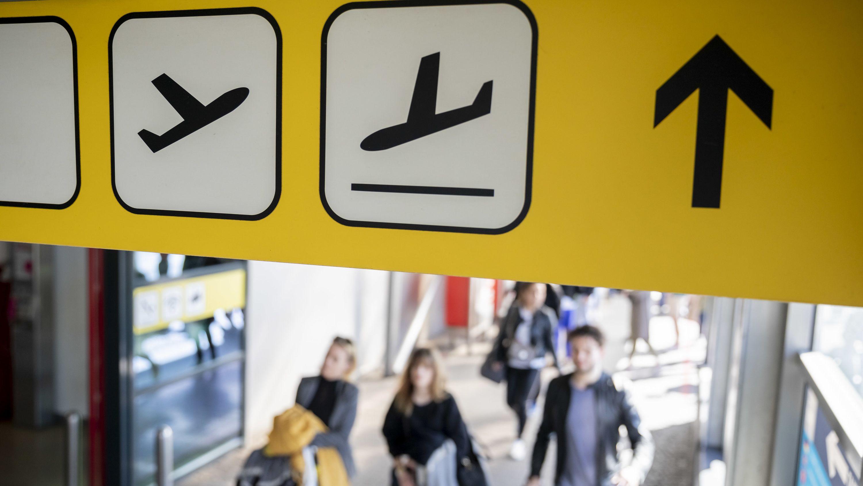 Passagiere laufen unter einem Schild mit den Zeichen für Abflug und Ankunft.