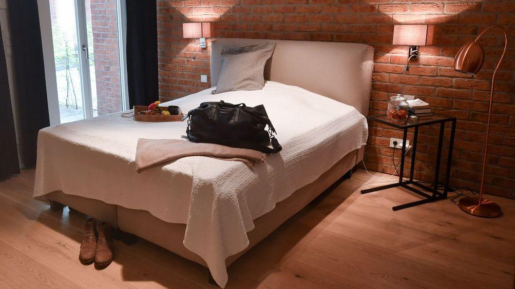 Zimmer einer Wohnung, die an Feriengäste vermietet wird. Eine Reisetasche ist in der Wohnung eines Airbnb-Gastgebers auf dem Bett abgestellt. Symbolbild für den Kampf von bayerischen Städten gegen Zweckentfremdung
