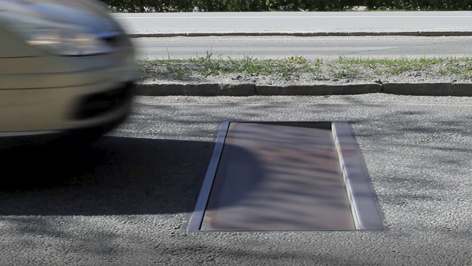 In einer Straße ist eine neuartige Temposchwelle zu sehen, die bei zu schnellem Fahren ein künstliches Schlagloch erzeugt.  Die Stadt Hanau will damit  Raser und Auto-Poser in der Innenstadt ausbremsen.