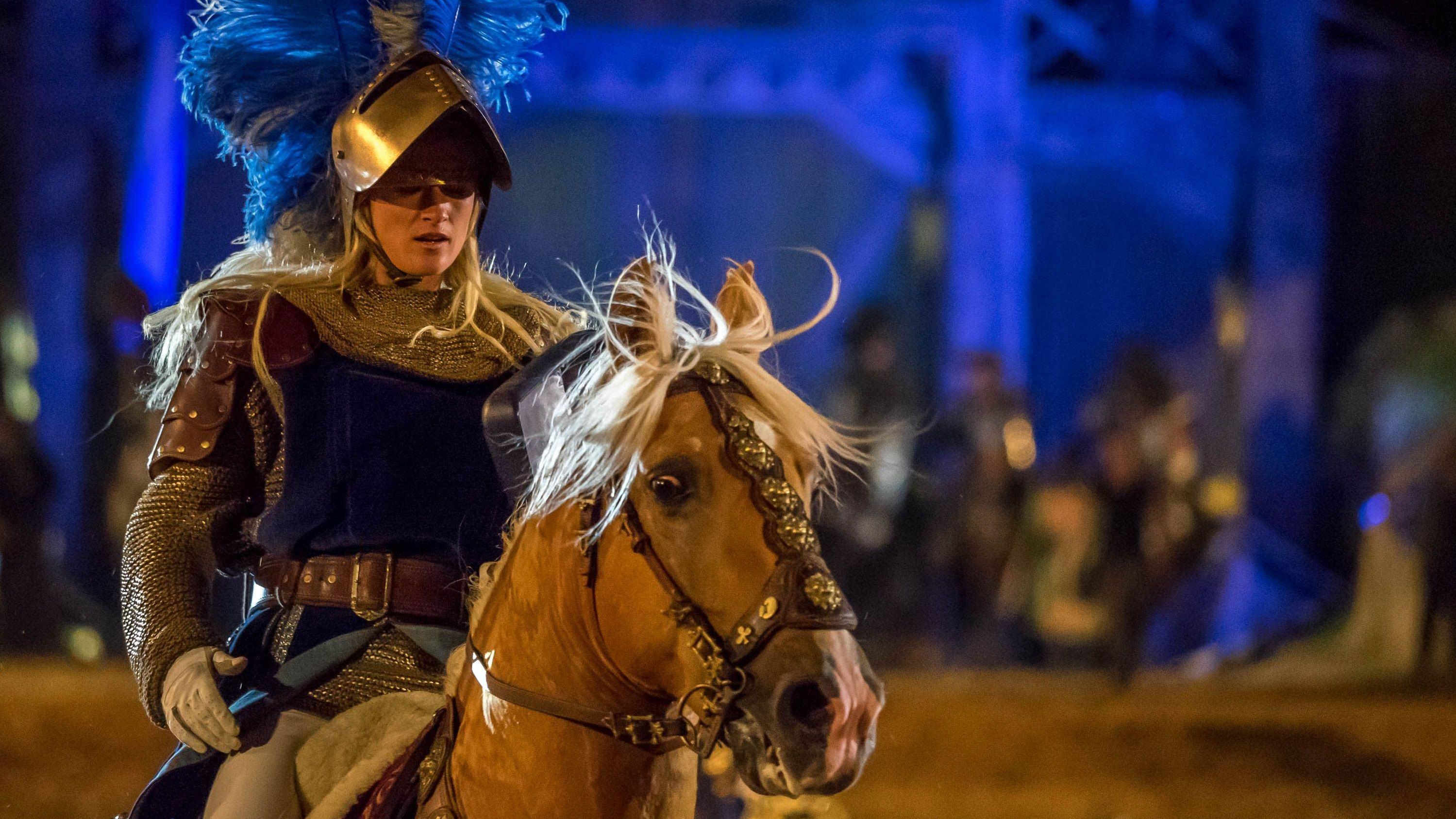 Eine Frau im Ritterkostüm hoch zu Ross.