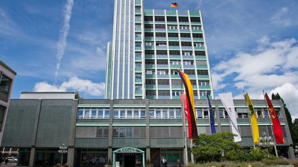 Vor dem Bayreuther Rathaus, einem Hochhaus, sind mehrere Fahnen aufgezogen, darunter die Deutschlandfahne.