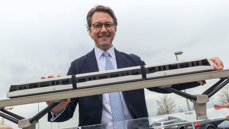 Andreas Scheuer (CSU), Bundesverkehrsminister steht nach einer Pressekonferenz, steht zum Start einer Machbarkeitsstudie für eine Magnetschwebebahn hinter einem Modell am Münchner Flughafen.